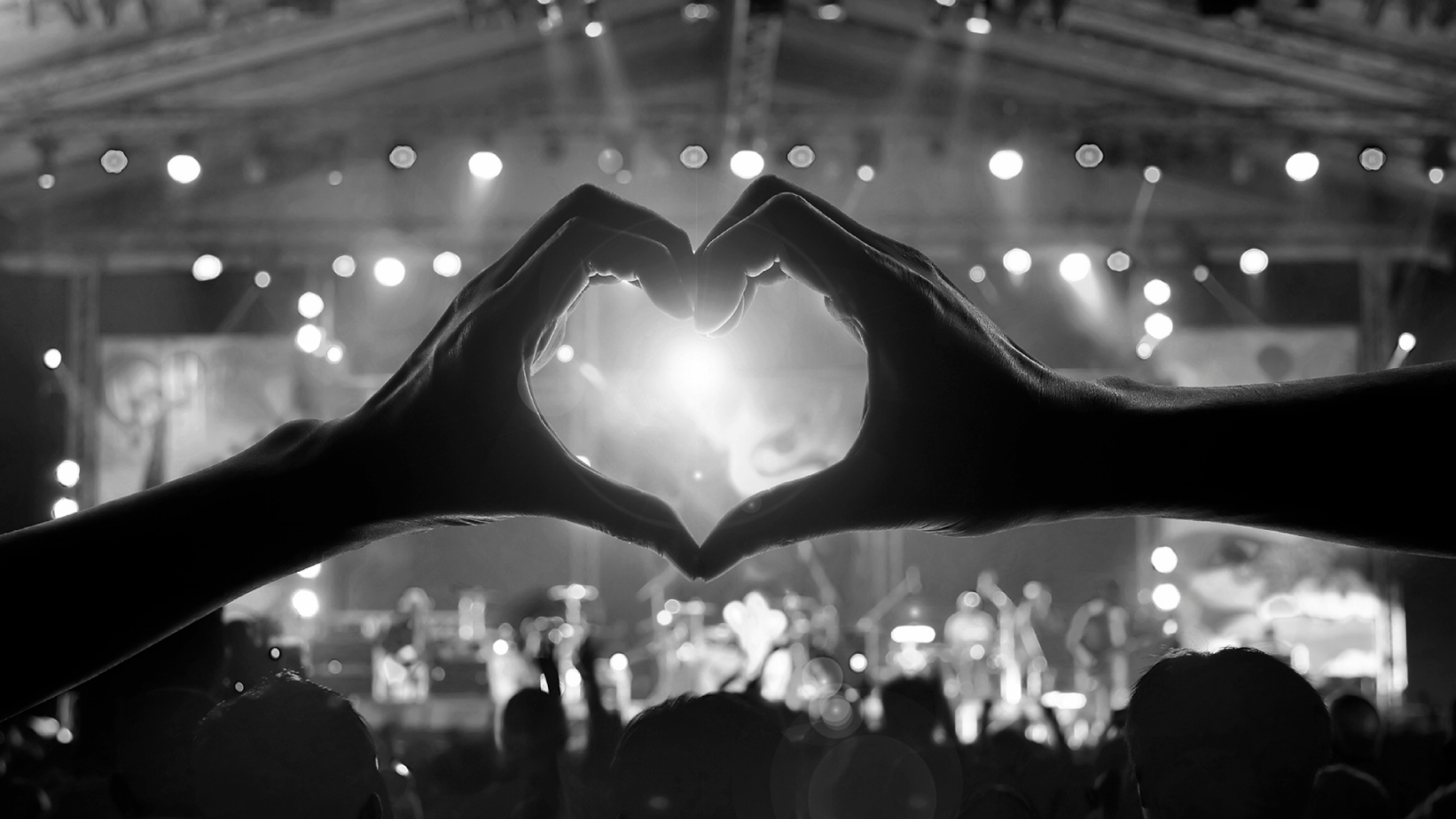 crowd of people watching rock show with hands making heart hands sign