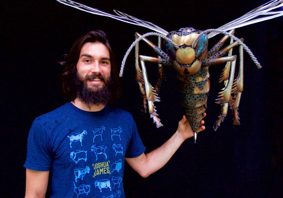 Artist Aiden Dale with metal wasp sculpture