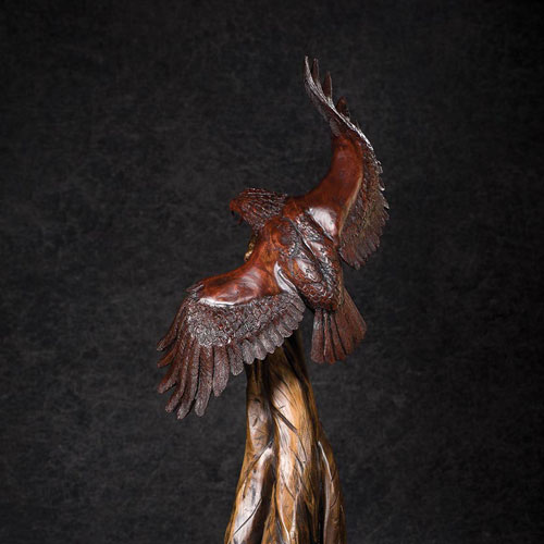 Back view of carved bald eagle perched on limb.