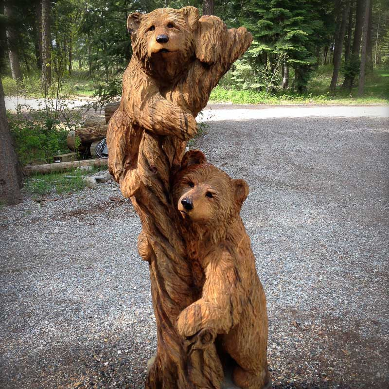 2 wood carved bears climbing on a tree