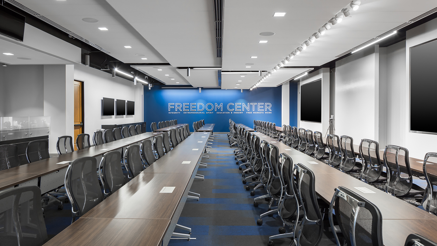 Photo of a large training room with three large flat-panel displays on one wall and one large video wall on the opposite side of the room.