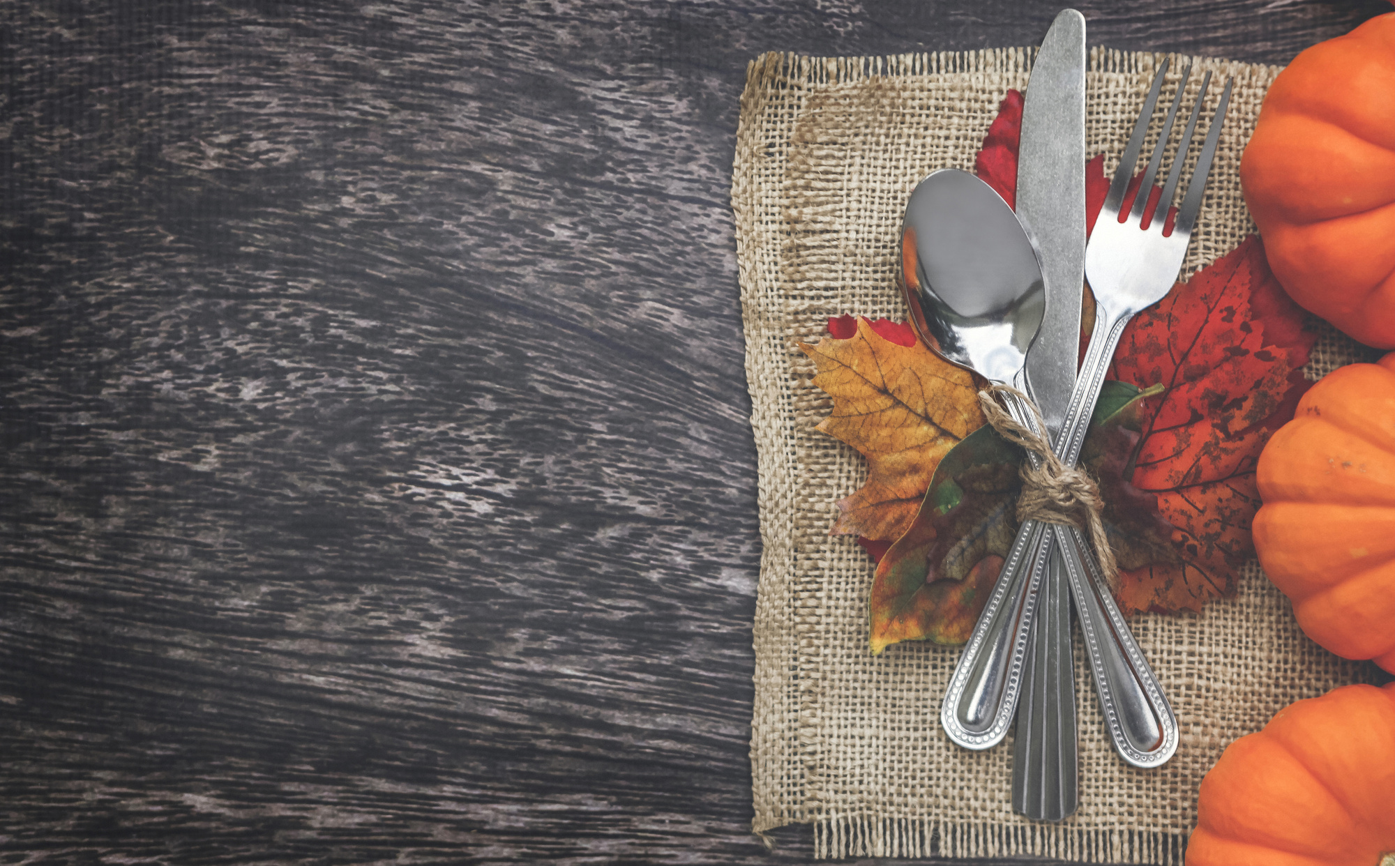 silverware next to pumpkins on table