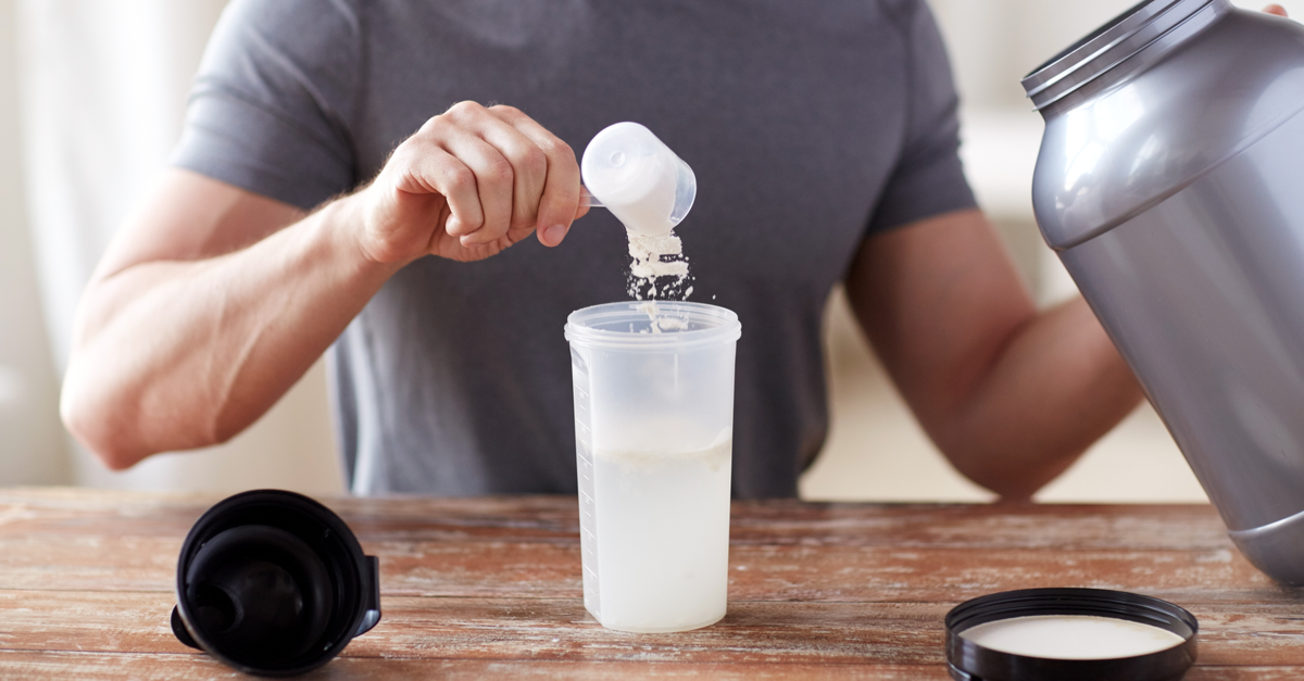 person pouring protein powder into a water bottle.