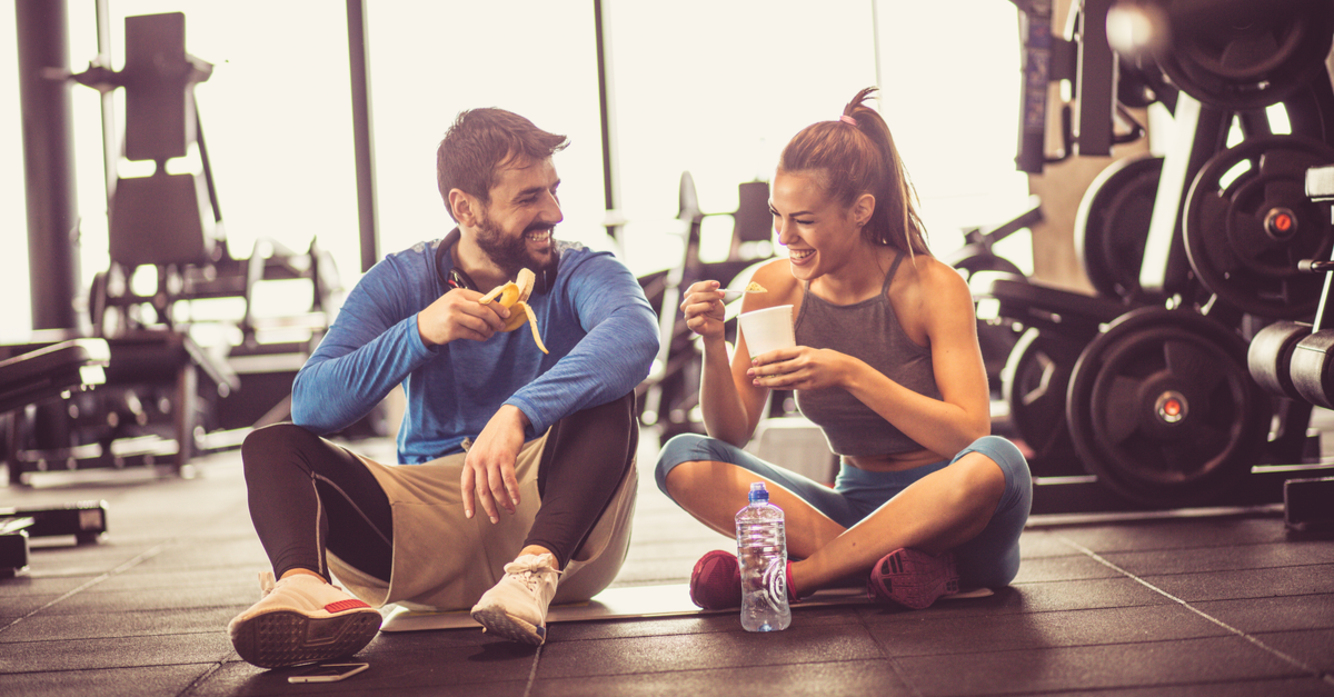 young woman and man sitting on the gym floor eating a banana and oatmeal