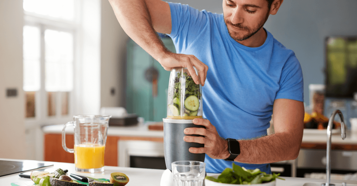 man in blue shirt blending spring mix and cucumber