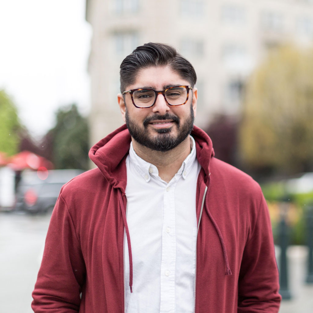Kashif, wearing a beard, glasses and a maroon hoodie