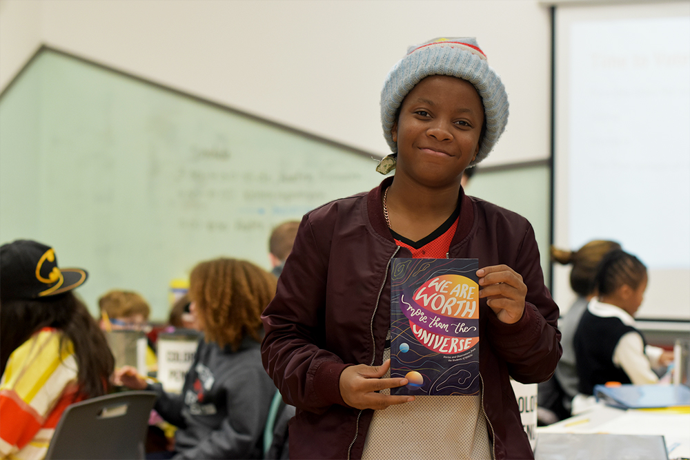 """Student holding """"We Are Worth More Than the Universe"""" book"""