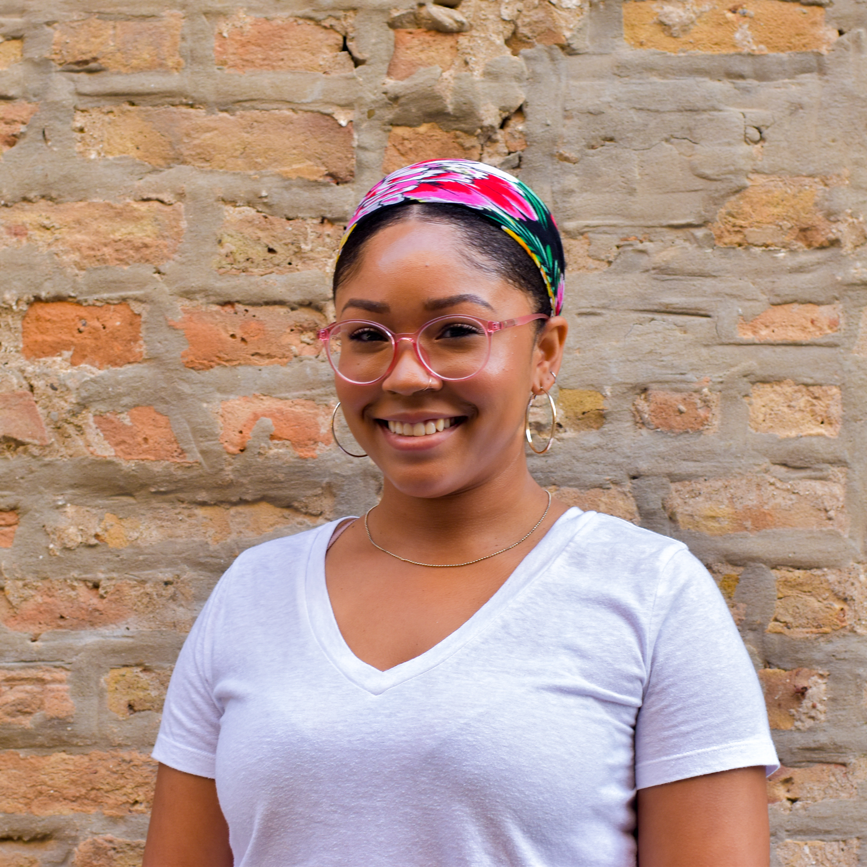 Portrait of Chinyere, smiling in front of a brick wall