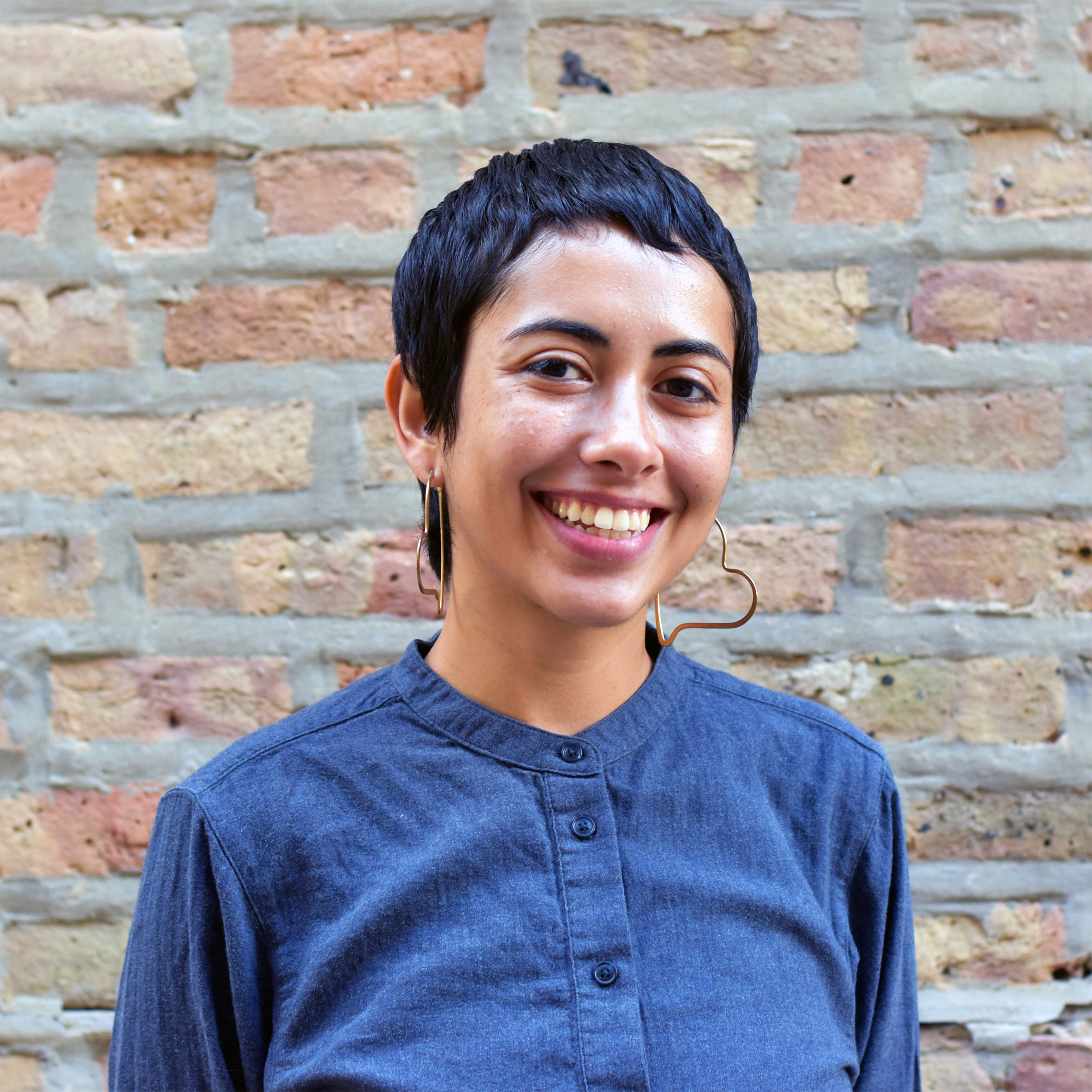 Portrait of Nohemi, smiling in front of a brick wall