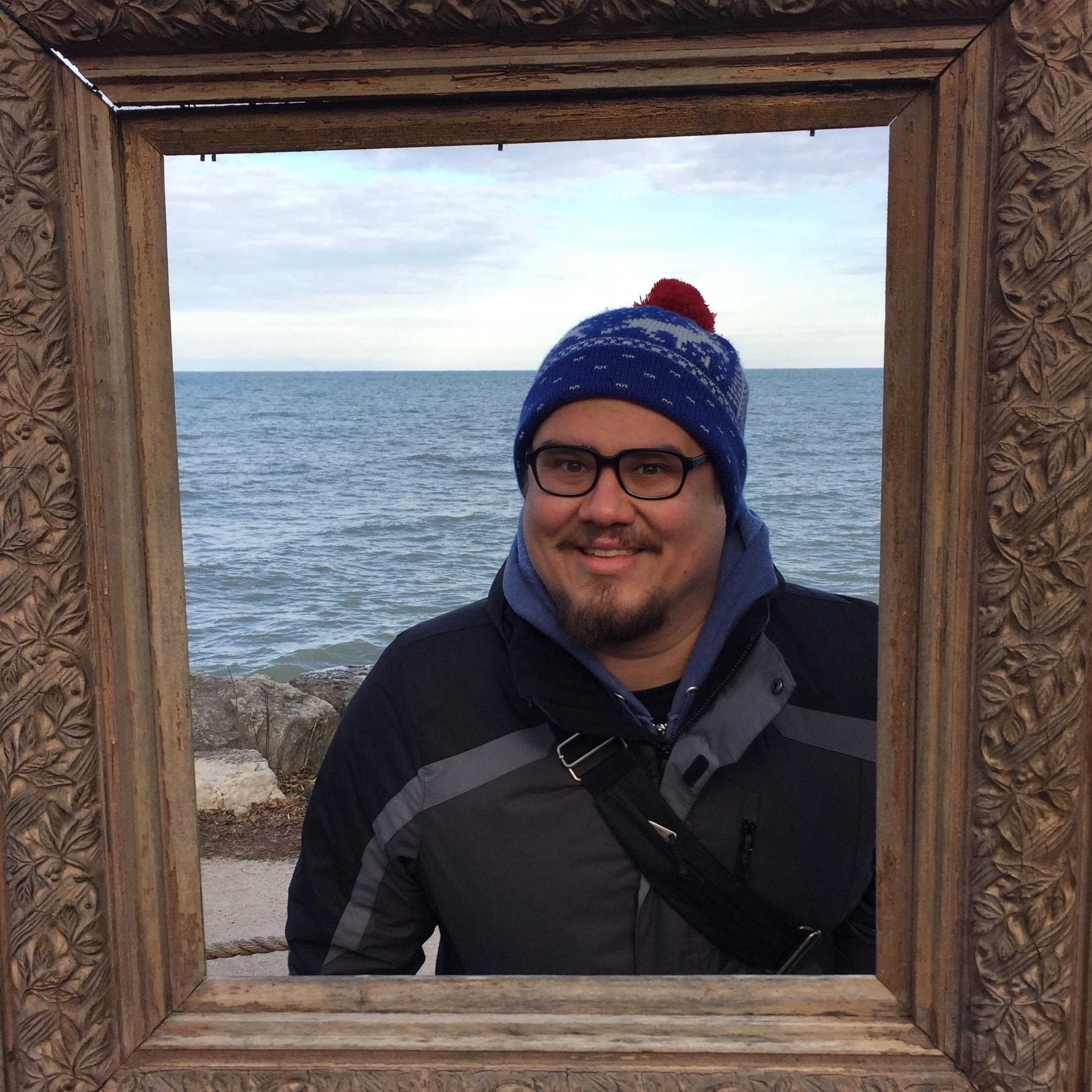 Tony smiling through a picture frame.