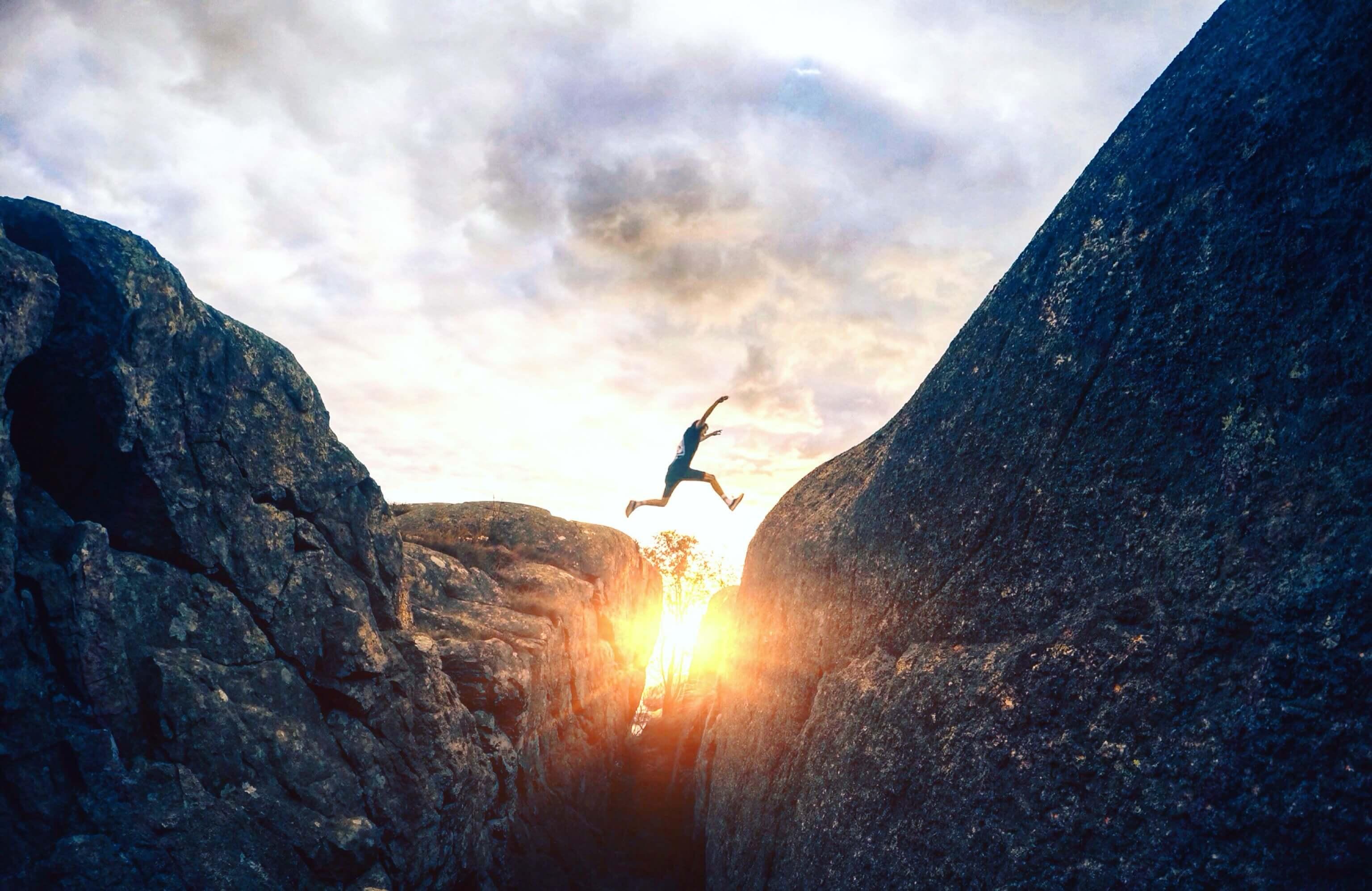 Pessoa saltando entre pedras