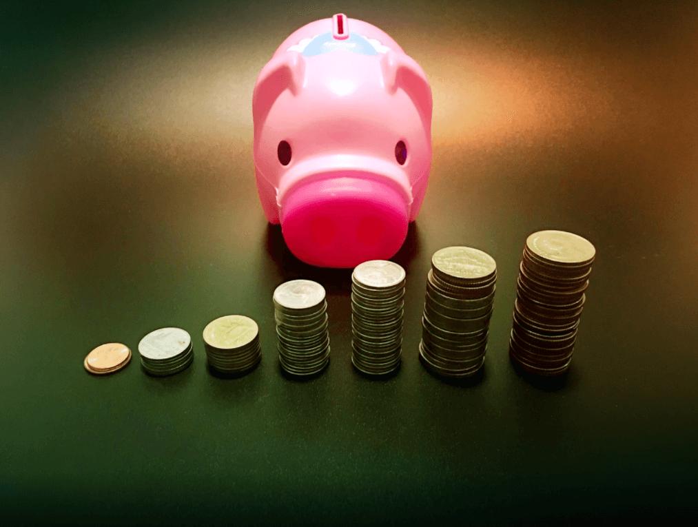 Cofrinho de porco rosa com moedas na frente