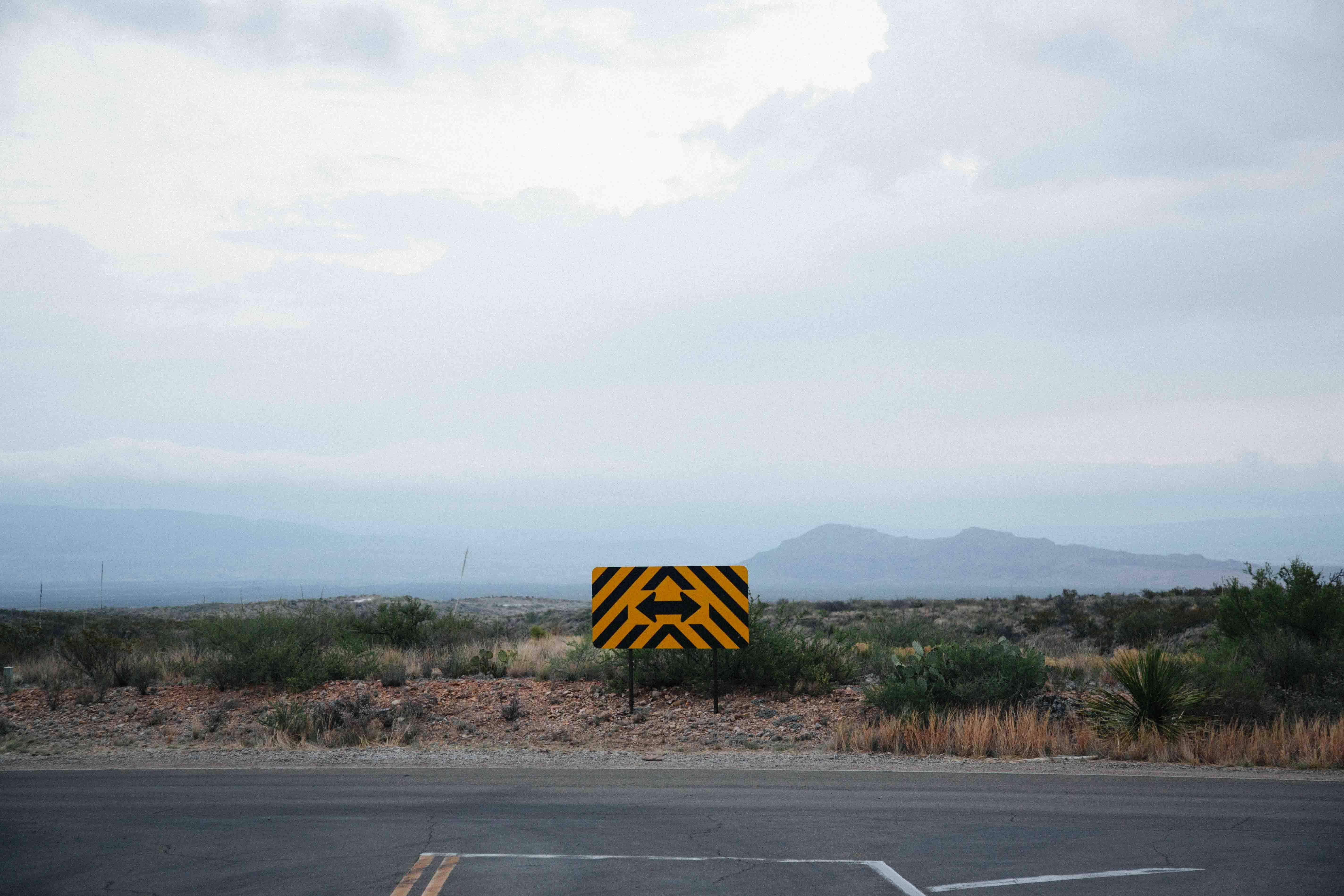 Estrada com uma placa sinalizando duas direções opostas
