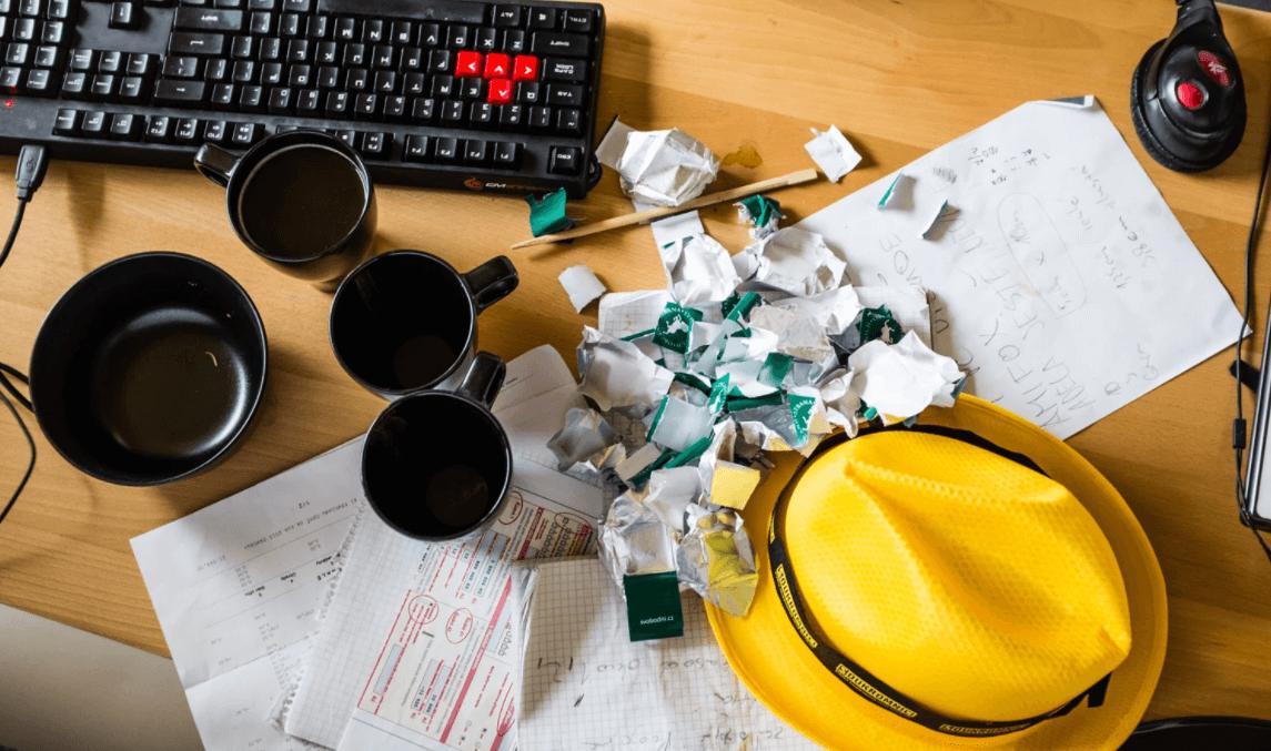 Mesa de escritório com papéis bagunçados e lixo espalhado