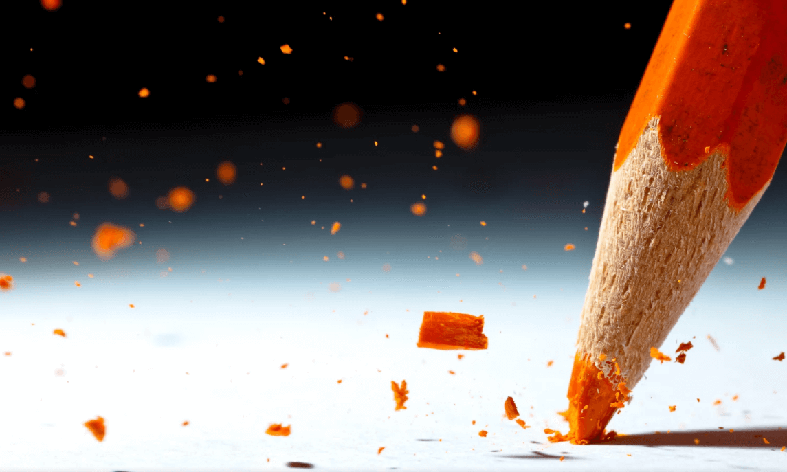 Lápis laranja com a ponta quebrada escrevendo na folha branca