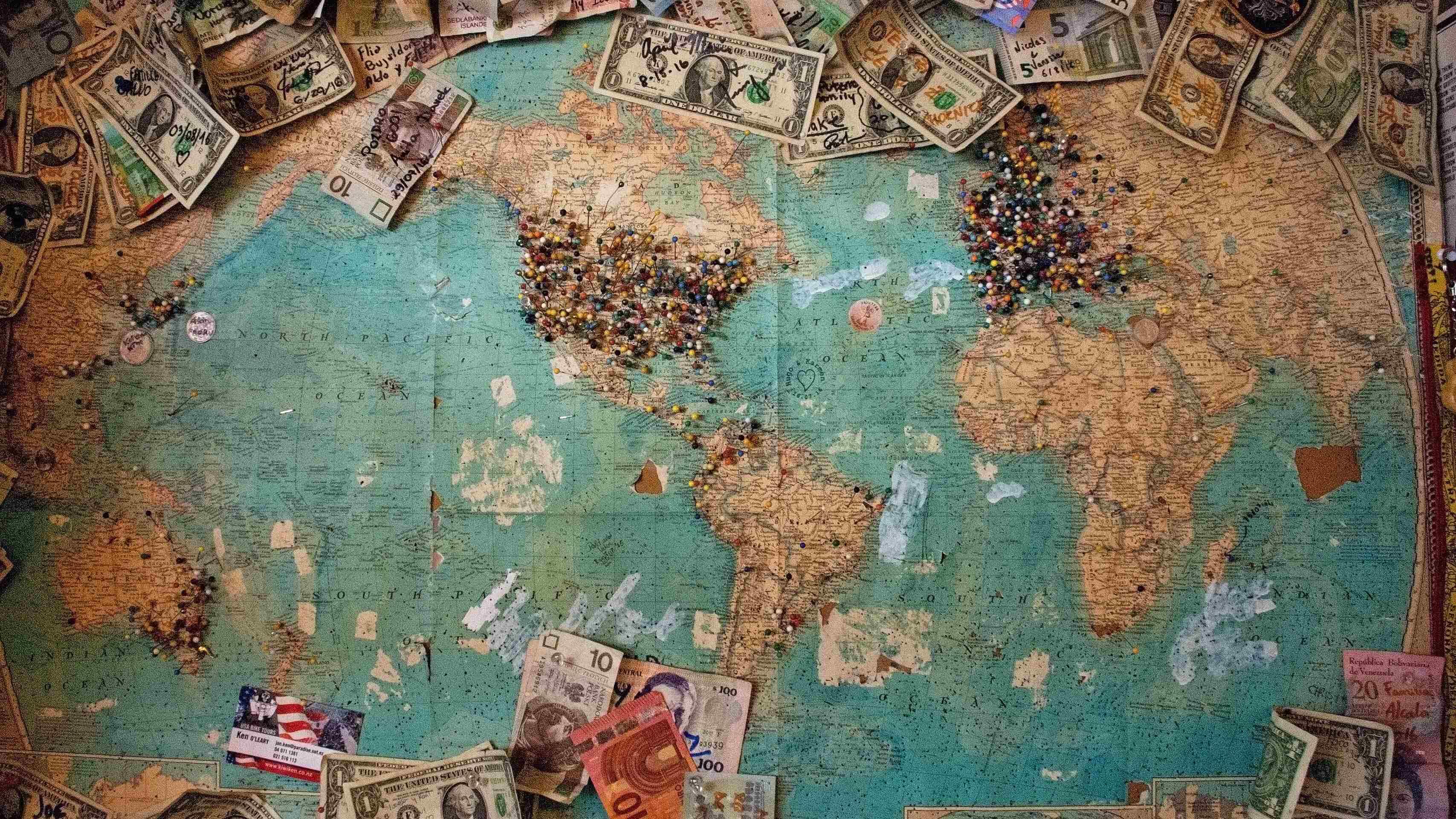 Mapa mundi com notas de dinheiro de vários países por cima