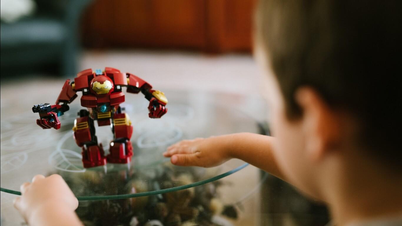 Garoto brincando com boneco do Homem de Ferro