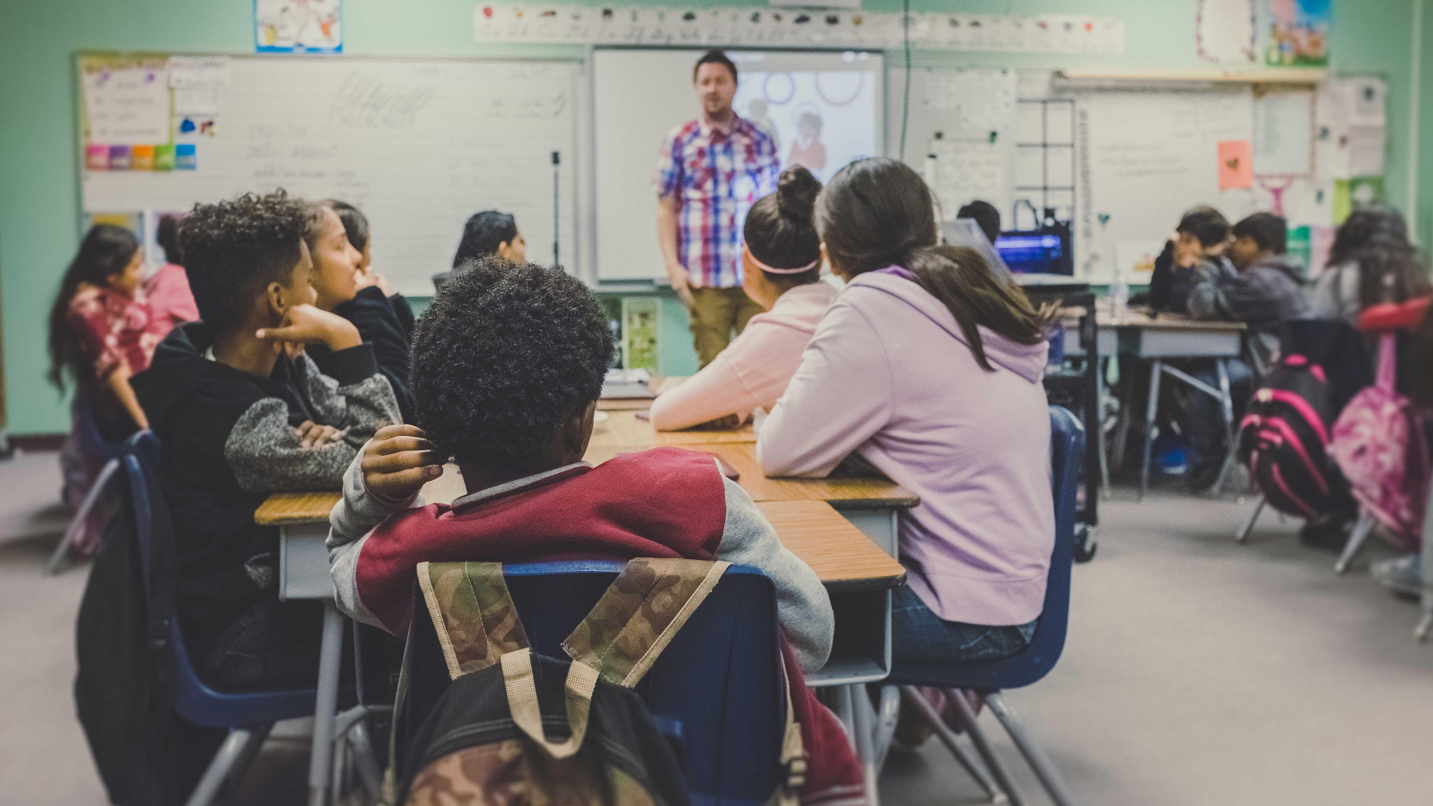 Alunos organizados em grupos na sala de aula
