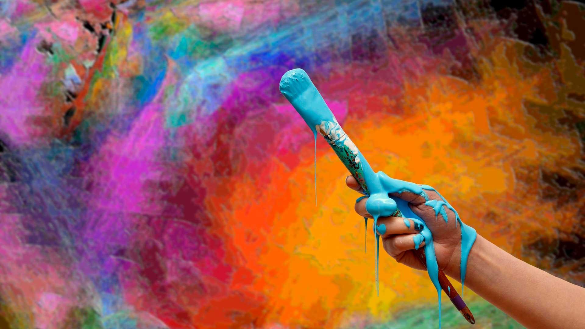 Mão segurando pincel sujo de tinta azul em frente a uma parede colorida.