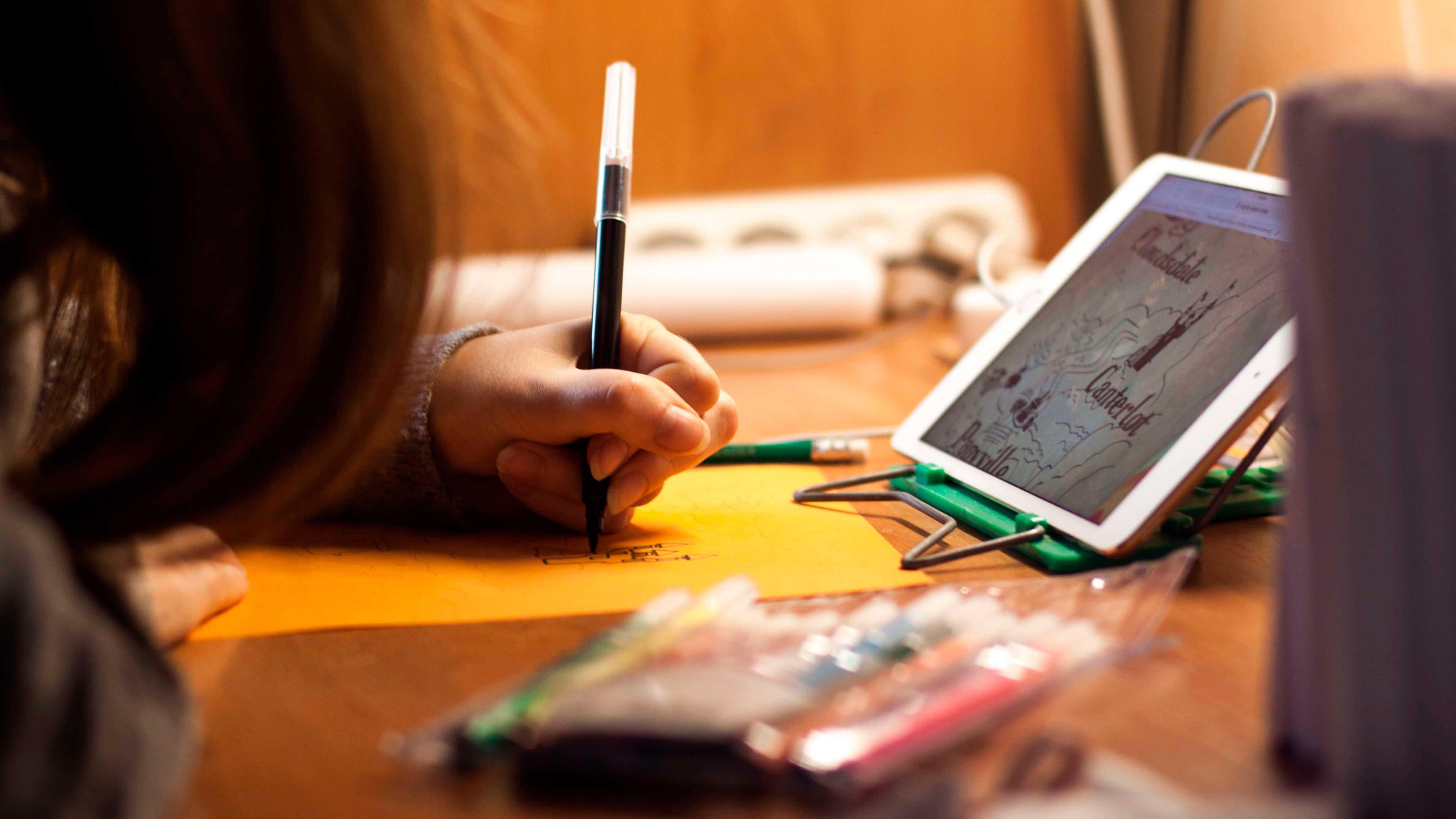Garota escrevendo em papel.