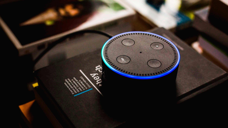 Como a IoT está criando um mundo hiperconectado? - Alexa, IoT da Amazon, em mesa de escritório cheia de livros.