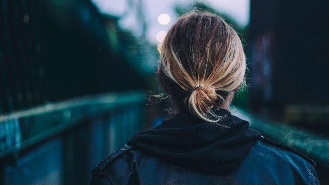 Qual é o seu propósito? - Mulher loira de costas em ponte.