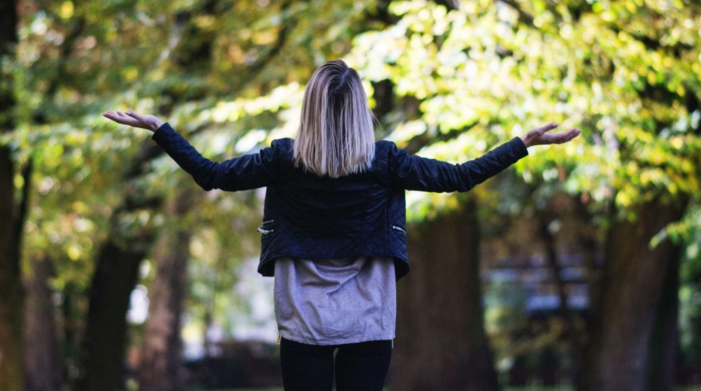 Mulher loira de costas com os braços abertos olhando para o céu, em parque.