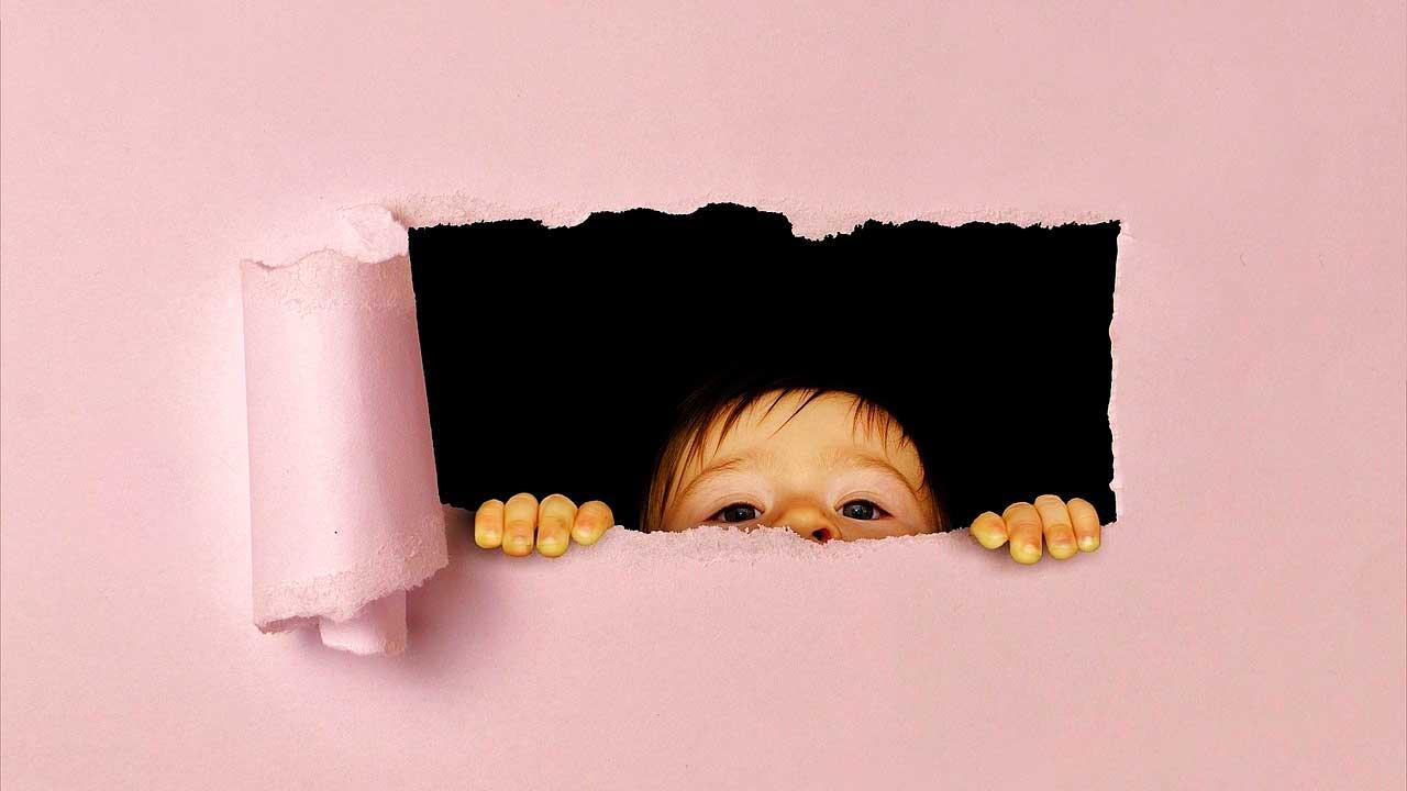 A saída existe, você só não viu... Ainda - Parede rosa com um buraco no qual encontra-se uma criança com olhar curioso.