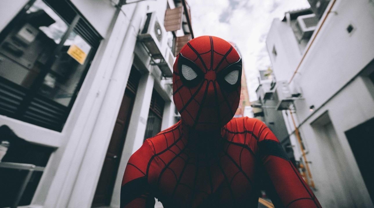 Foto do rosto com máscara do super herói Homem Aranha e prédios de fundo