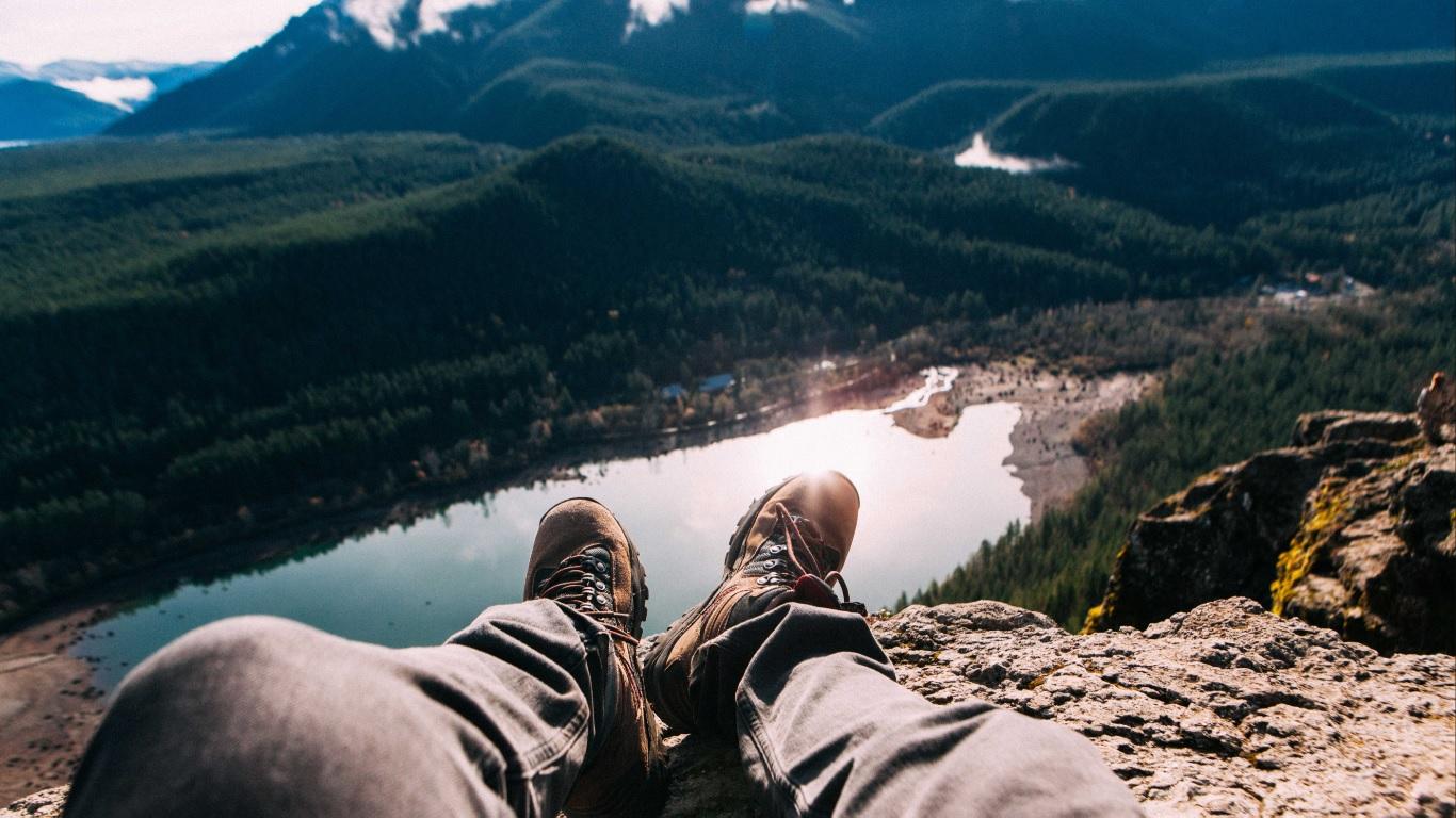 Paisagem natural de montanhas com picos nevados e árvores, pernas masculinas usando calça jeans provavelmente pertencentes a quem tirou a foto.