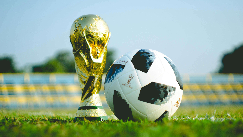Gramado do campo de futebol com a taã da Copa do Mundo no chão ao lado de uma bola de futebol