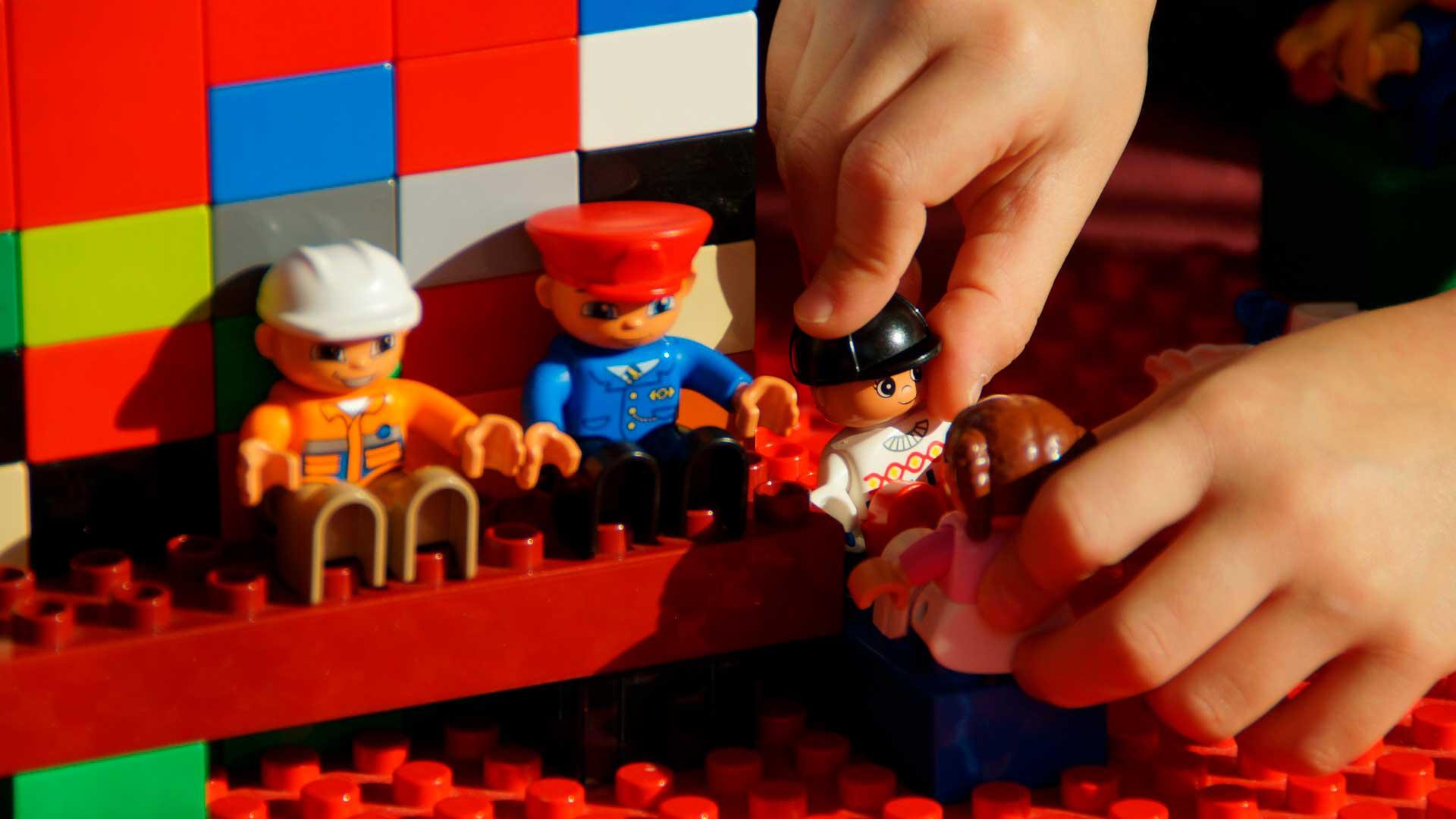 Peças de LEGO com tres bonecos sentado e uma boneca em pé nas mãos da criança