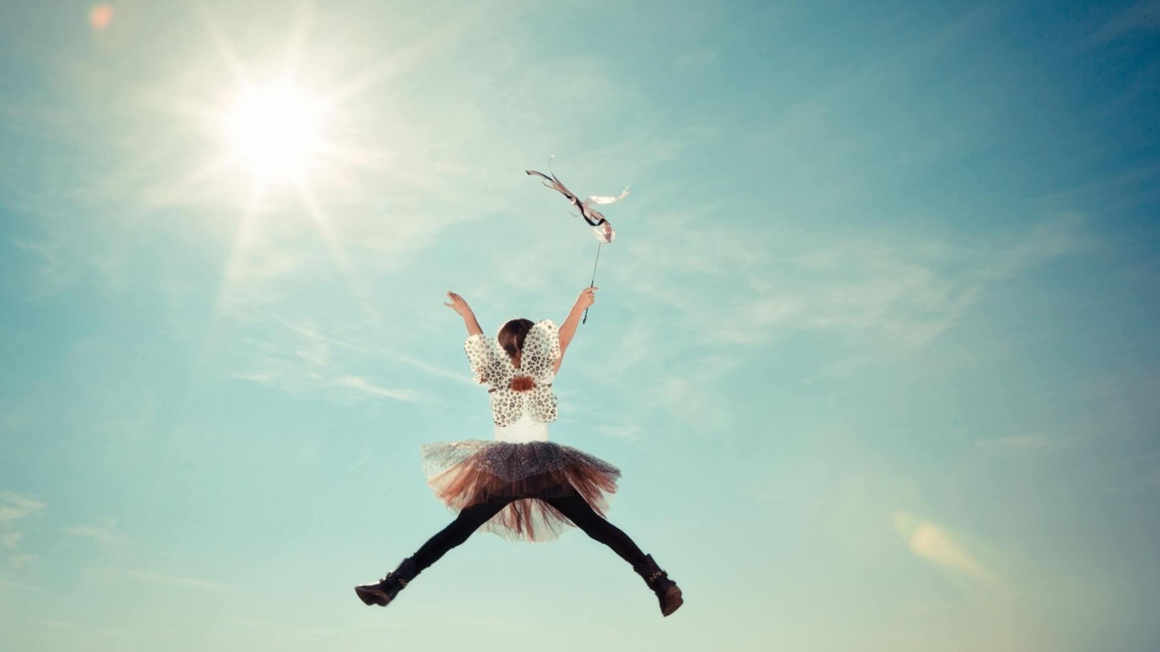 Porque nutrir a criatividade das crianças facilita com que elas encontrem seu propósito de vida quando adultas? - Menina vestida de fada com uma varinha na mão saltando.