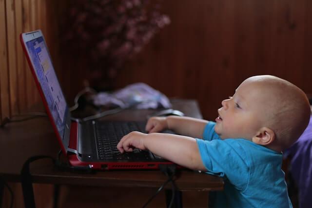 Bebê brincando no notebook