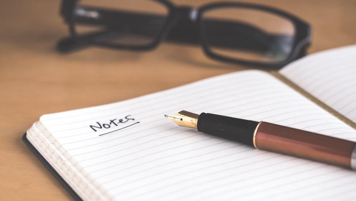 Caderno de anotações aberto com uma caneta sob a folha e um óculos de fundo