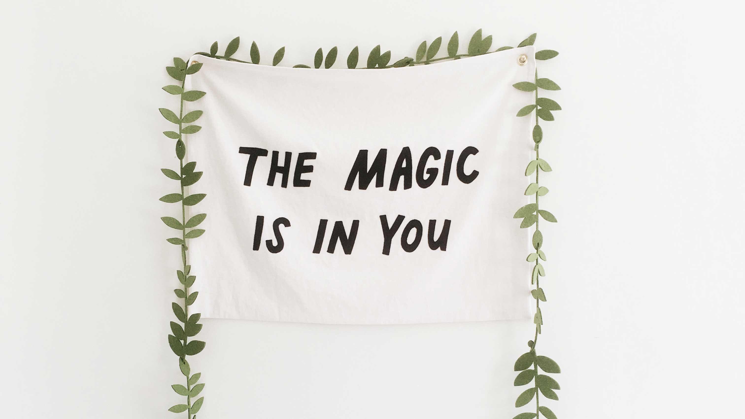 """Pano com a frase """"Tha Magic is in You"""" pregado a parede com folhas ao redor, como as de uma árvore."""