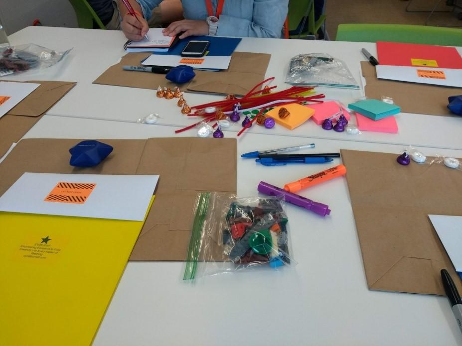 Mesa com cartolinas, peças de lego, canetas coloridas e post-its
