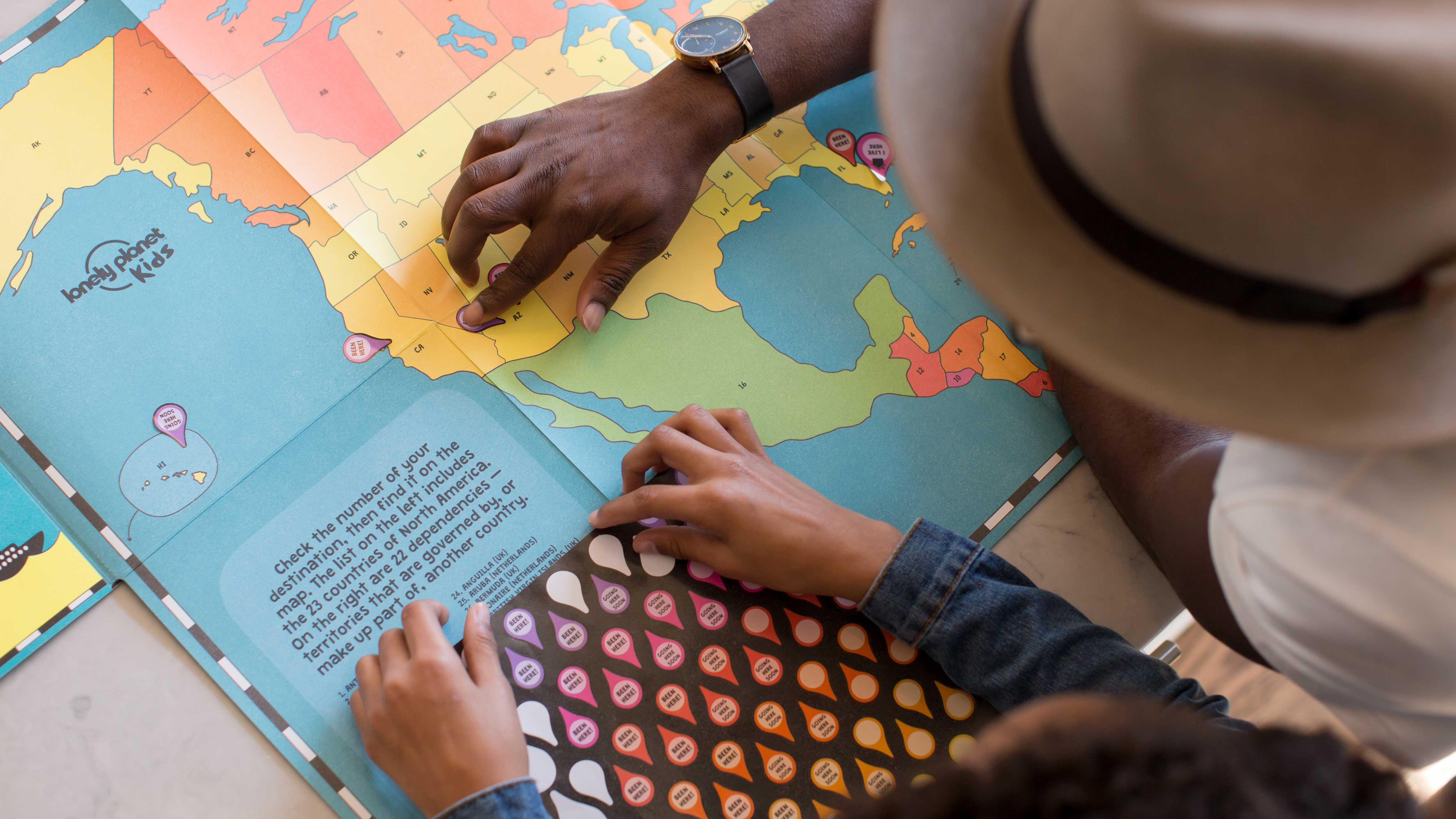 Na imagem vemos uma folha do mapa mundi com um pai mostrando para seu filho os Estados Unidos.