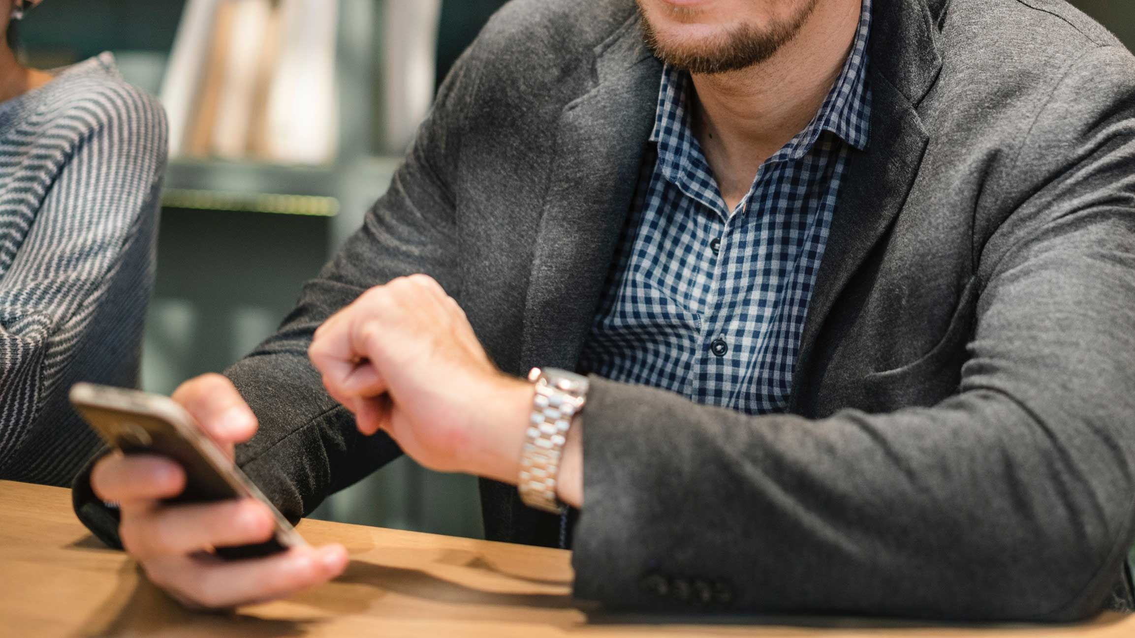 Mãos de um homem segurando um celular.