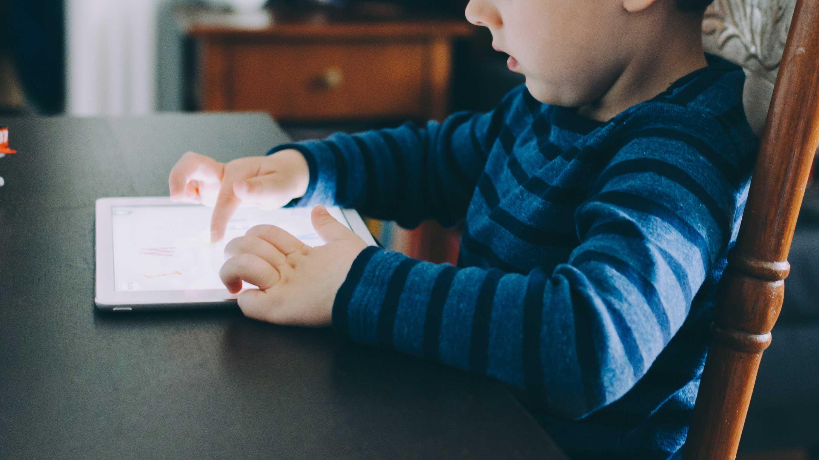 Menino sentado à mesa mexendo em seu tablet