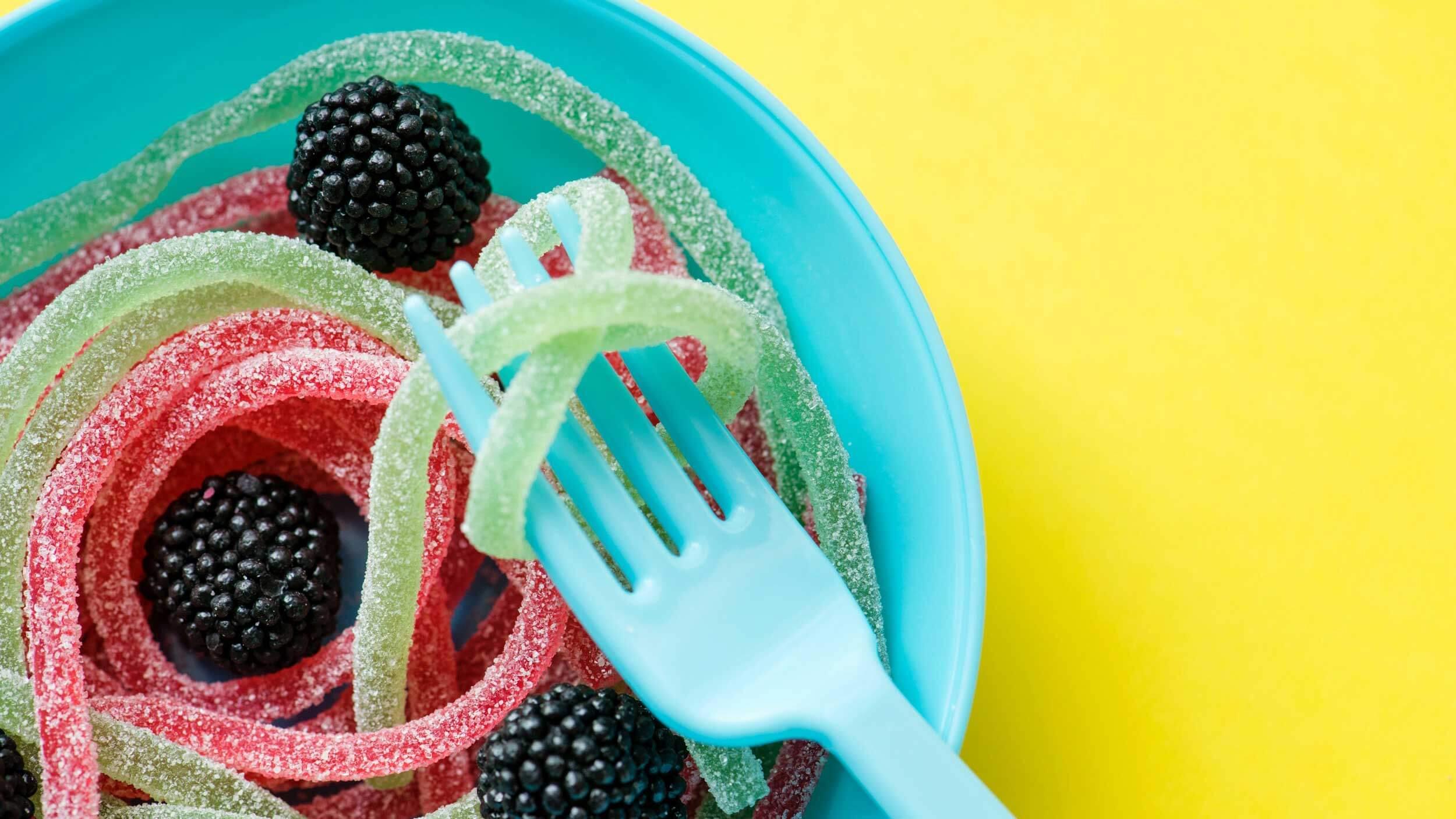Prato azul com balas de gelatina em formato de amora e minhocas com um garfo levantando uma como se fosse um macarrão