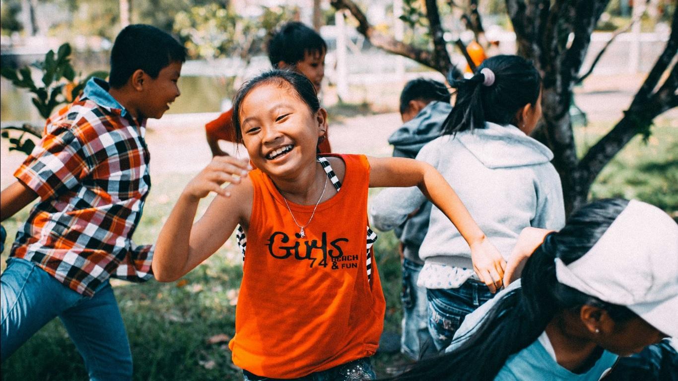 A importância do brincar na educação infantil - Crianças correndo e sorrindo, aparentemente brincando de pega-pega.