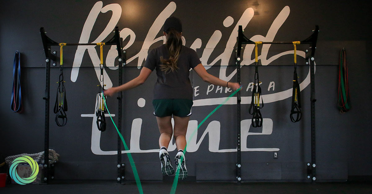 Woman in office gym with skipping rope working out
