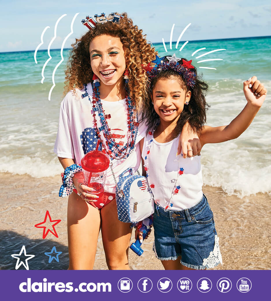 Two girls wearing 4th of July-themed clothing and accessories on a beach
