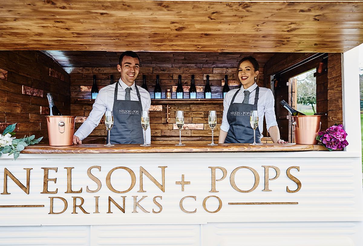 Bartenders standing behind bar smiling