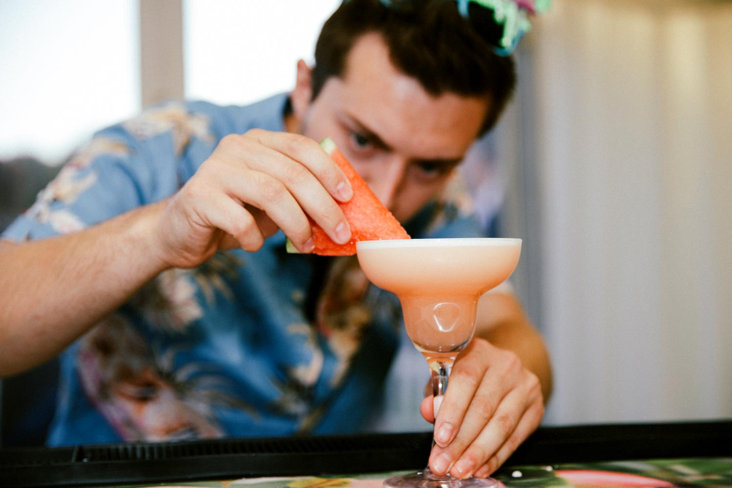 bartender garnishing cocktail with watermelon