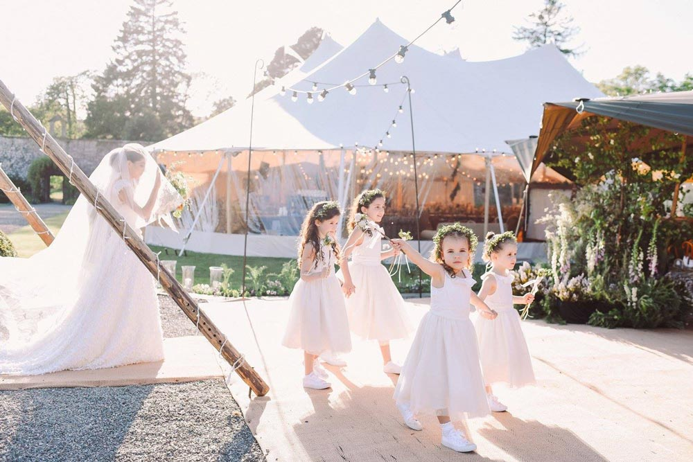 Bride and flower girls in front of tipi