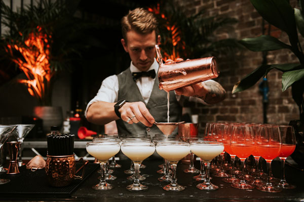 Professional cocktail barman pouring drinks