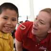 Dr. Elkins helps a young patient hear on Mission Trip to Chimbote, Peru