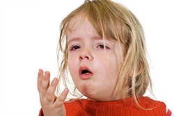 Toddler with red, itchy eyes coughing due to an allergic reaction.